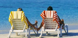 Couple Holding Hands on Beach Chairs